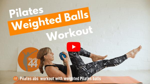 women doing 1 leg stretch holding Pilates balls