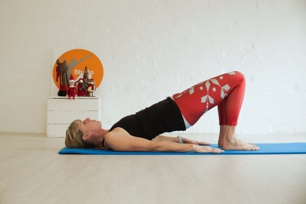 Women lying on a blue mat with a blck vest top on red christmas leggings doing the Pilates move the shoulder bridge