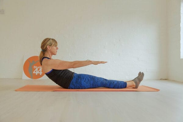 women doing a Pilates move the roll up. wearing blue leggings and black vest top