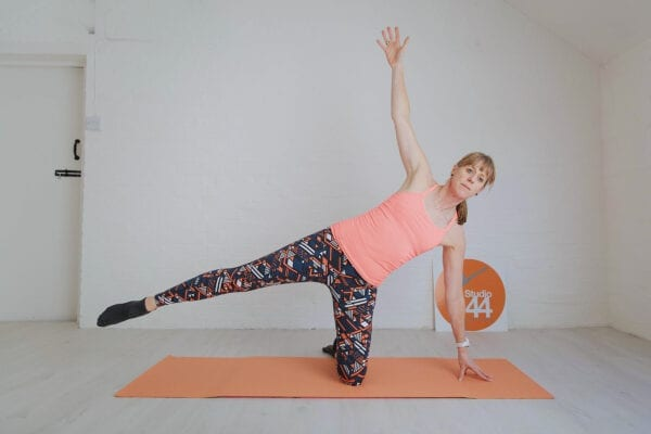 Women on one knee with other leg out to side doing Pilates side kick