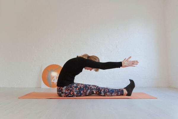 Women sitting on an orange mat with kegs out straight and curving forward into the Pilates move the spine stretch