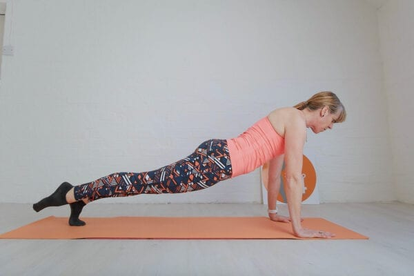 White background with a women on her toes and straight arms doing a leg pull prone for Pilates for runners