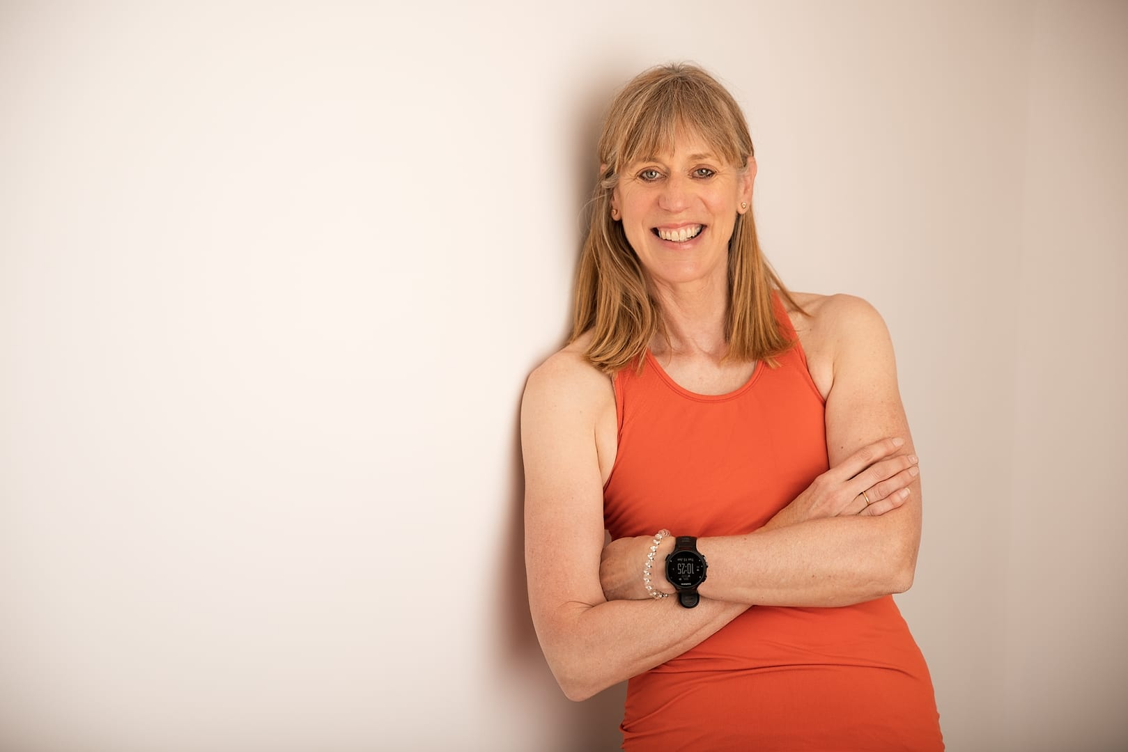 Louise from Studio 44 Pilates standing by a wall smiling