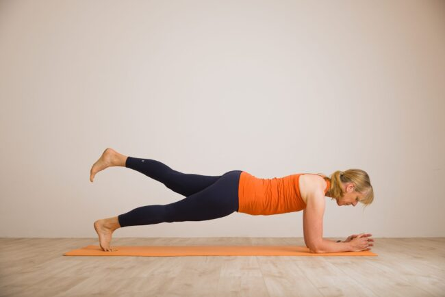 Louise Humphrey demonstrating the Pilates exercise the plank with one leg off the ground