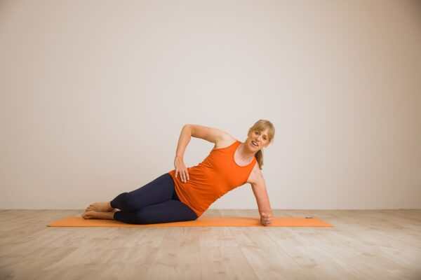 Louise lying sideways on an orange mat up on her elbow ready to do the clam